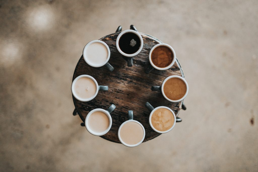 An image of eight cups of coffee set in a circle. Each cup has various levels of cream, altering its color.